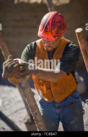Dirty mid-adult construction worker wearing a helmet and safety glasses while working on a construction site. - Stock Photo