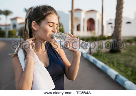 Joyful happy woman in sportswear drinking water with closed eyes in sunny morning on street of tropical city. Training, workout, motivation, attractive model, fitness - Stock Photo