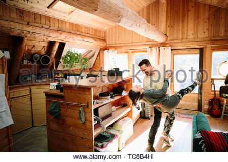 Playful couple dancing in cabin - Stock Photo