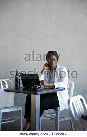 Portrait confident young businesswoman working at laptop in cafe - Stock Photo