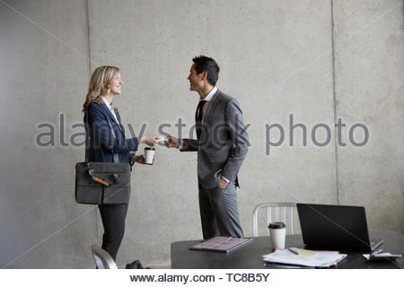 Business people networking, exchanging business cards in meeting - Stock Photo