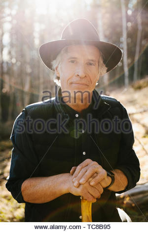 Portrait confident mature man hiking in sunny woods - Stock Photo