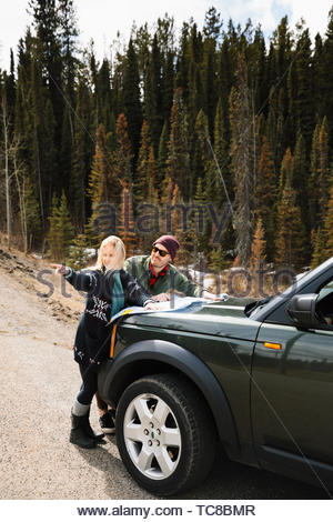 Couple looking at map on hood of SUV at remote roadside - Stock Photo