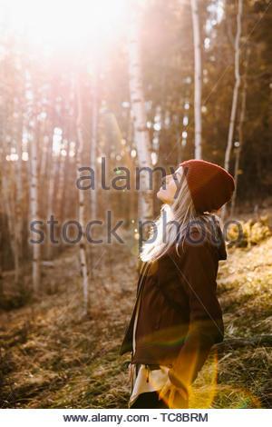Serene woman basking in sunlight, hiking in woods - Stock Photo