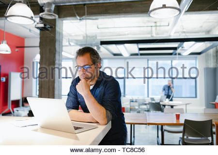 Focused businessman working at laptop in coworking space - Stock Photo