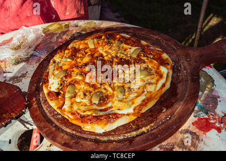Rough home made vegetarian pizza with tomatoes, basil, olives and cheese made on grill - Stock Photo