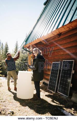 Couple installing solar panels and rain barrel on cabin - Stock Photo