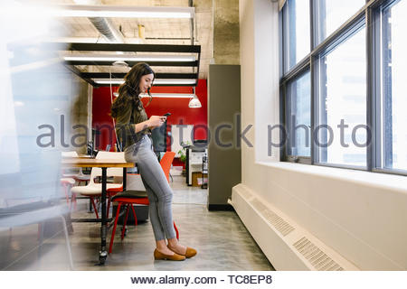 Businesswoman using smart phone in office - Stock Photo