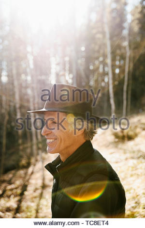 Smiling mature man with hat hiking in sunny woods - Stock Photo