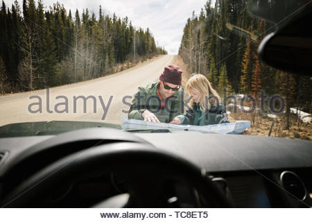 Couple looking at map on hood of SUV at sunny remote roadside - Stock Photo