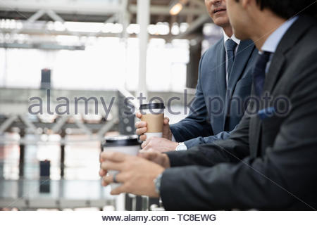 Businessmen with coffee talking on office balcony - Stock Photo
