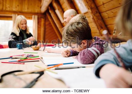 Family coloring and playing cards at cabin table - Stock Photo