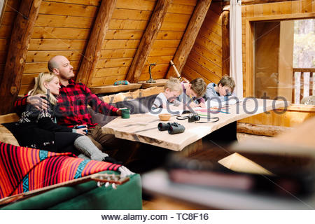 Family relaxing and coloring in cabin - Stock Photo