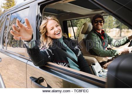 Carefree woman enjoying road trip in SUV - Stock Photo