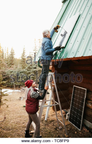 Couple installing solar panels on cabin roof - Stock Photo