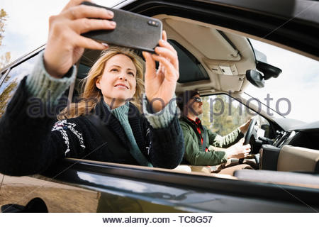 Woman with camera phone riding in car - Stock Photo