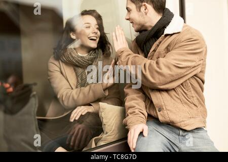 young happy laughing teenage couple separated by window, trying to touch hands, in Cottbus, Brandenburg, Germany - Stock Photo