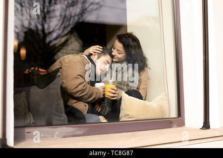 young affectionate teenage couple behind window hanging out in café, in Cottbus, Brandenburg, Germany - Stock Photo