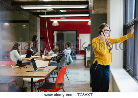 Businesswoman talking on smart phone at office window - Stock Photo