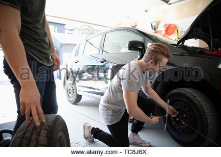Teenage boy changing car tire in garage - Stock Photo
