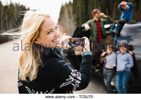 Portrait happy mother with camera phone photographing family at roadside - Stock Photo