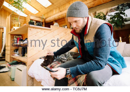 Man with dog using smart phone in cabin - Stock Photo
