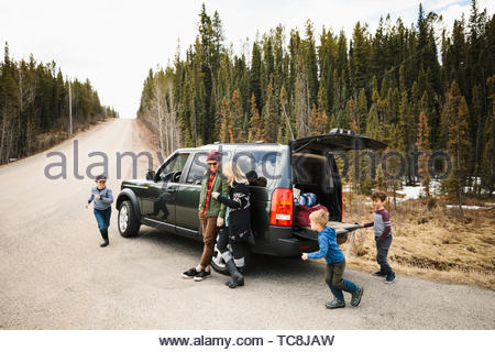 Family standing and playing outside SUV at remote roadside - Stock Photo