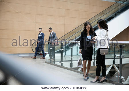 Business people talking at escalators in modern office - Stock Photo