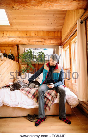 Man with dog on cabin bed - Stock Photo