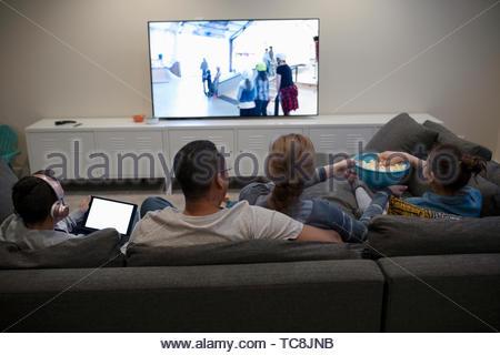 Family watching movie, eating popcorn on sofa - Stock Photo