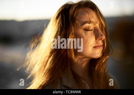 young emotive woman outdoors in warm sunlight, closed eyes, hair blowing in wind, joy, in Cottbus, Brandenburg, Germany