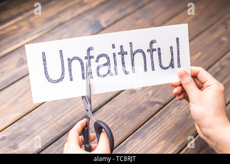 woman cuts white paper with word unfaithful on table - Stock Photo
