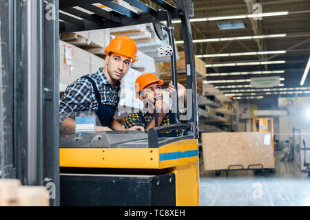 attentive worker sitting in forklift machine near his indian colleague talking on walkie talkie - Stock Photo