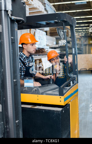 handsome, attentive worker in helmet sitting in forklift machine near indian colleague talking on walkie talkie - Stock Photo