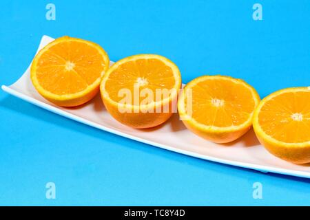 Oranges on a plate with blue background - Stock Photo