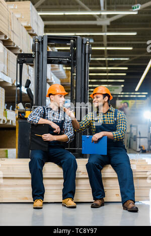 two smiling multicultural workers with clipboards talking while sitting on plywood - Stock Photo