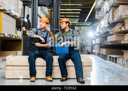 two multicultural workers talking while sitting on plywood in warehouse - Stock Photo