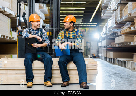 two multicultural workers smiling and talking while sitting on plywood in warehouse - Stock Photo
