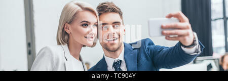 panoramic shot of cheerful business partners taking selfie in office together - Stock Photo