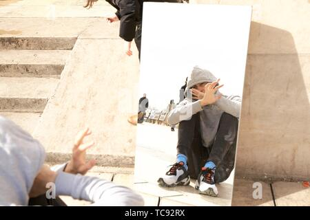 young man hiding himself from his mirror image in public, in Paris, France. - Stock Photo