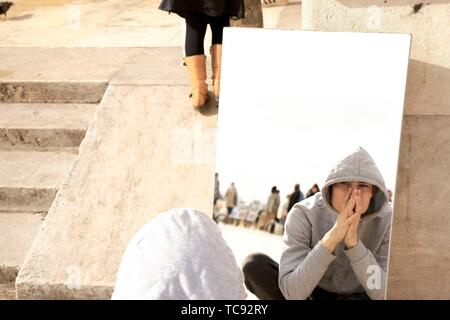teenager with folded hands looking at himself in mirror, in Paris, France. - Stock Photo