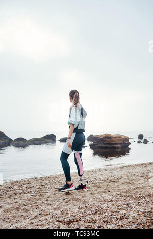 Your body can stand almost anything. Back view of young disabled athlete woman in sportswear with prosthetic leg is standing on the beach. Disabled Sportsman. Motivation - Stock Photo