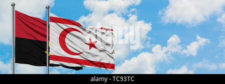 Angola and Northern Cyprus flag waving in the wind against white cloudy blue sky together. Diplomacy concept, international relations. - Stock Photo