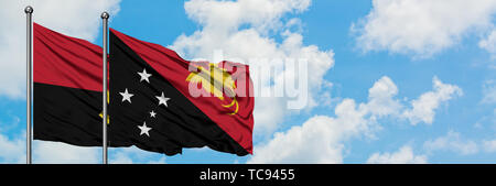 Angola and Papua New Guinea flag waving in the wind against white cloudy blue sky together. Diplomacy concept, international relations. - Stock Photo