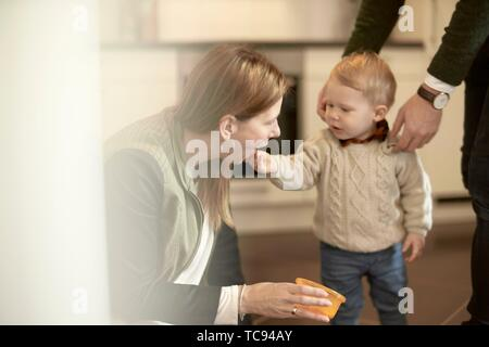 baby toddler child feeding mother in kitchen at home, in Cottbus, Brandenburg, Germany. - Stock Photo