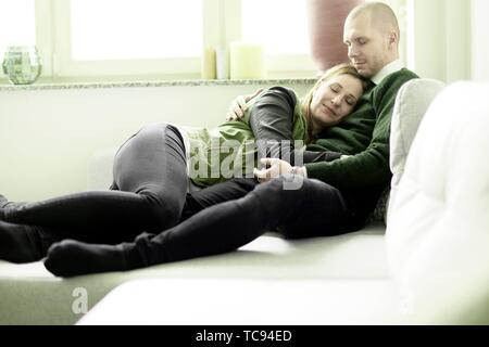 couple cuddling together on couch in living room, feeling emotive relaxed, bonding, mature woman nestling with man, in Cottbus, Brandenburg, Germany. - Stock Photo