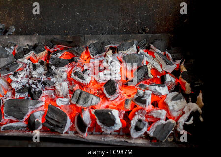 Bright hot coals and burning woods in bbq grill pit. Glowing and flaming charcoal, barbecue, red fire and ash. Weekend recreation background. Close-up - Stock Photo