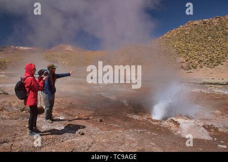 Watching a geyser erupt along the Rio Blanco, El Tatio, San Pedro de Atacama, Chile. - Stock Photo