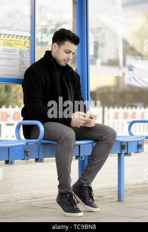 young man waiting for public transport at bus station, using smartphone, in Munich, Germany. - Stock Photo
