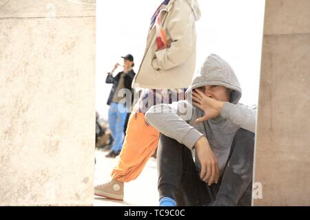 teenager hiding himself in public, in Paris, France. - Stock Photo